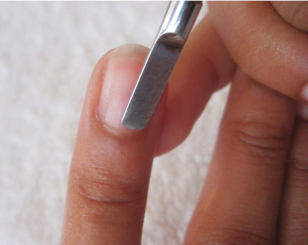 Apply cuticle oil (or olive oil) in cuticle area and place hands in warm water for cuticles to soften for 10 minutes. Gently by using cuticle pusher, push back skin from your cuticles and away from nails to help nails grow stronger.
